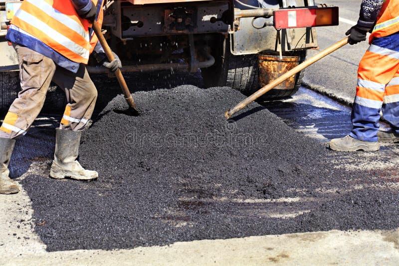 Den funktionsdugliga besättningen fördelar jämnt varm asfalt med skyfflar manuellt på den reparerade platsen av vägen arkivbild