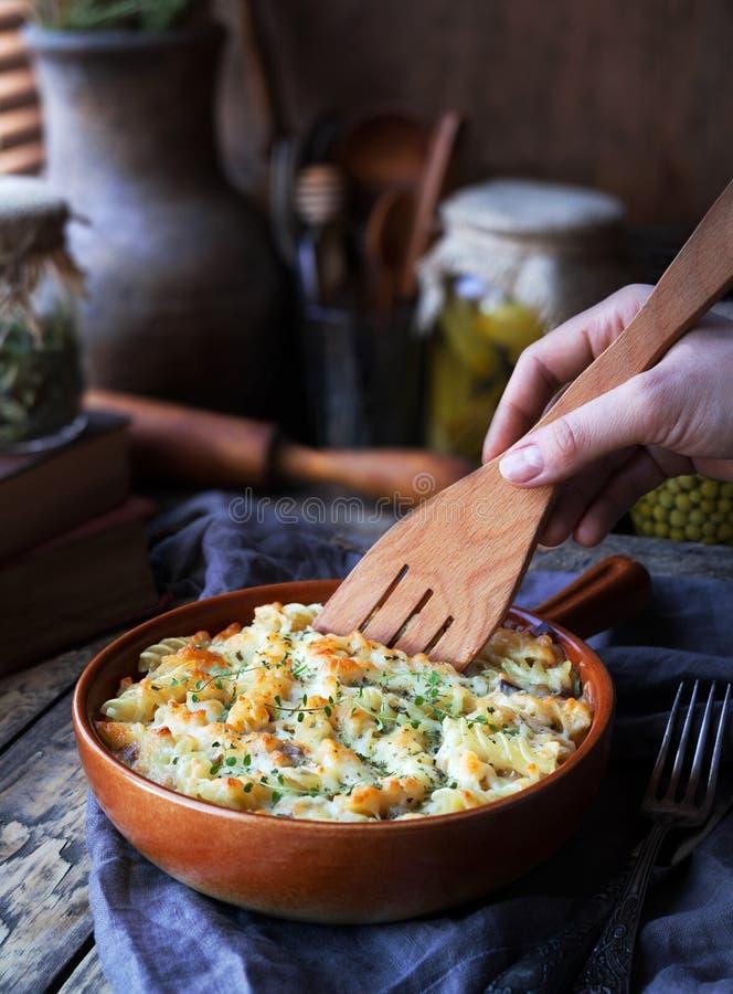 Den Fusilli pastaeldfasta formen med höna, den blåa ostdoren och kryddor tjänade som på en leraplatta på ett träköksbord in royaltyfri bild