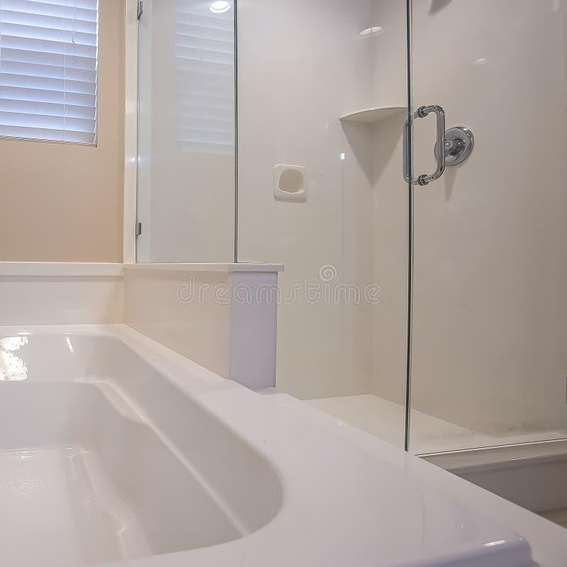 Den fyrkantiga rambadruminre av ett hem med det skinande badkaret och den exponeringsglas walled duschen stannar arkivfoto