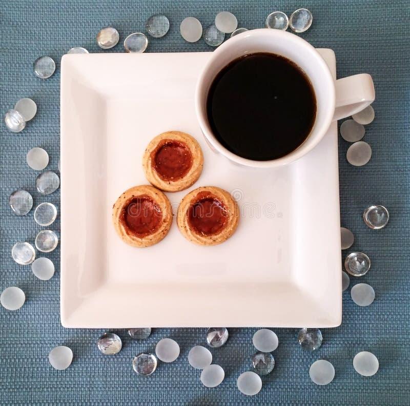 Den fyrkantiga vita plattan och rånar med kakor och svart kaffe arkivfoto