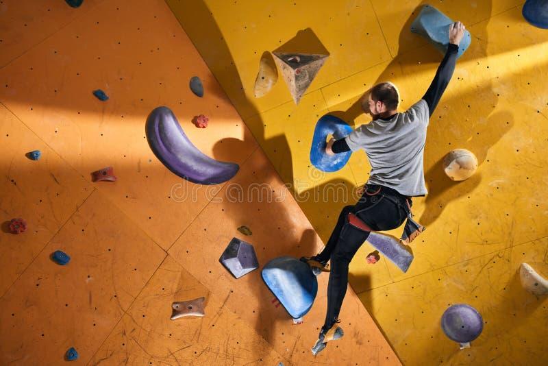 Den fysiskt utmanade mannen som klibbas på svårt, vaggar väggen i bouldering idrottshall arkivfoton