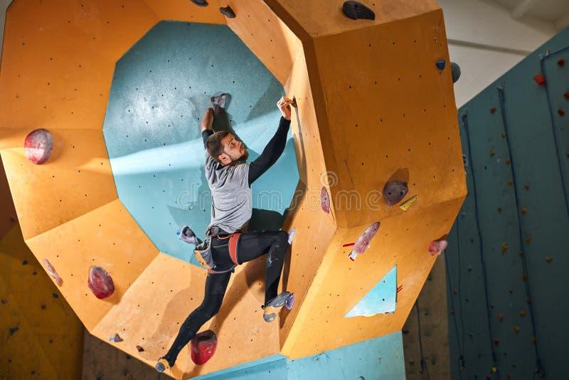 Den fysiskt utmanade unga idrottsmannen som flyttar sig upp på runda-Shape, vaggar väggen royaltyfri bild