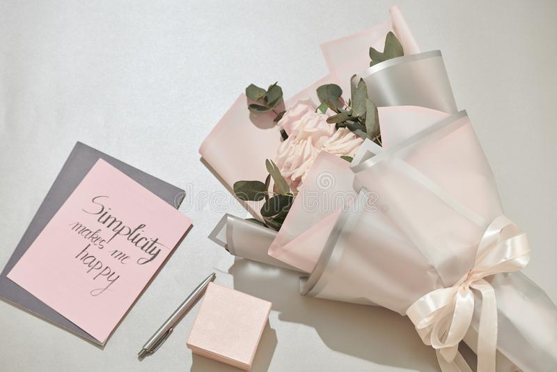 Den g?vaasken, ringklockan och rosa f?rger steg blommor p? den vita tabellen royaltyfria foton