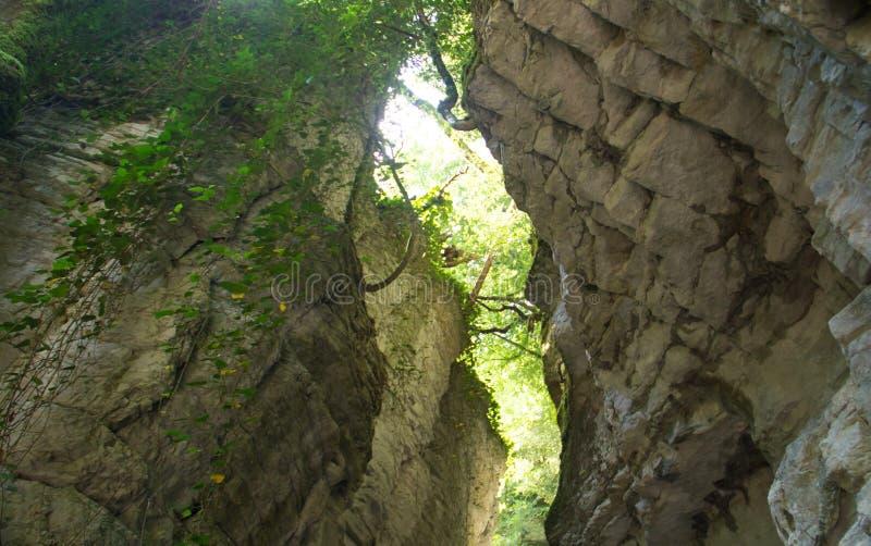Den gömda vita steniga klyftan i sikten av dalen under med ett smalt vaggar korridoren royaltyfri fotografi