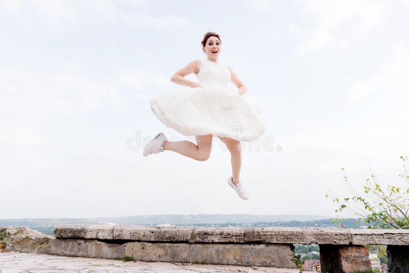 Den galna bruden hoppar och hänger i himlen mot bakgrunden av cityscapen av en liten semesterortstad i det nordligt arkivfoton