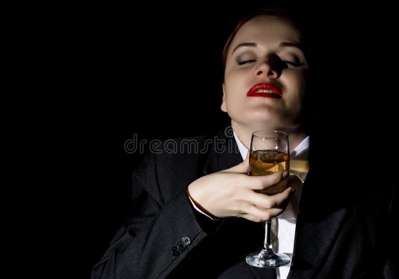 Den galna kvinnan i en dräkt för man` s dricker champagne, vilt skratt royaltyfri bild