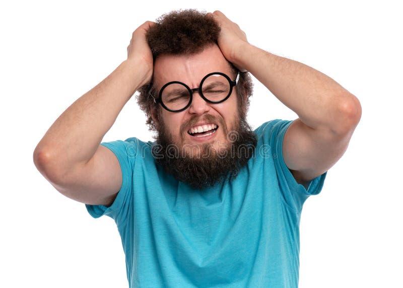 Den galna skäggiga mannen har huvudvärk royaltyfria foton