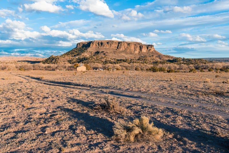 Den gamla Adobekyrkan ställde in i ökenlandskapet nedanför Black Mesa och Sangren de Cristo Berg nära Santa Fe som var ny - Mexik arkivbild