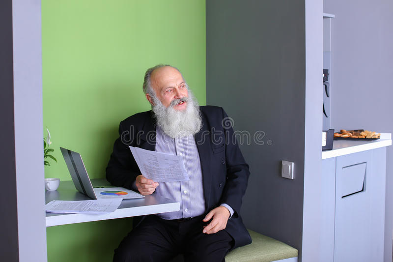 Den gamla affärsmandirektören eller arbetsledaren beräknar minimum balanc arkivfoto