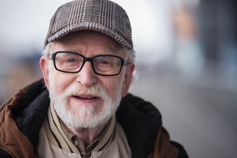 Den gamla angenäma mannen poserar med obetydligt leende arkivbild