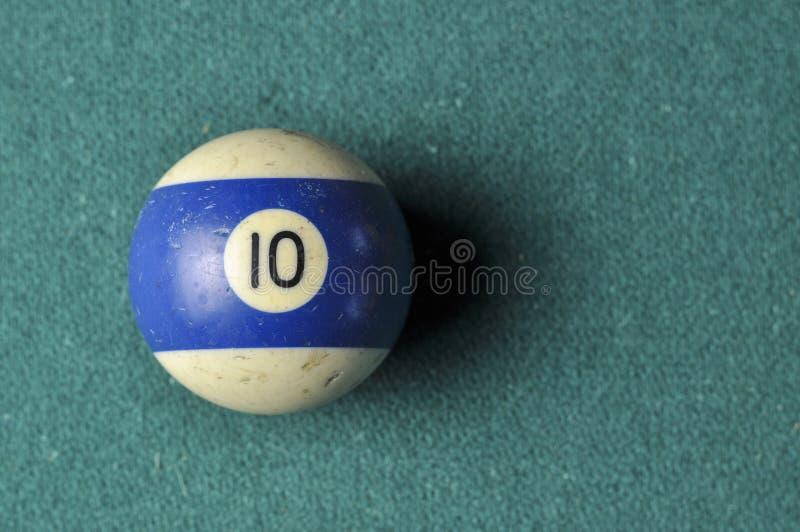 Den gamla billiardbollen nummer 10 gjorde randig vitt och blått på den gröna billiardtabellen, kopieringsutrymme arkivbilder