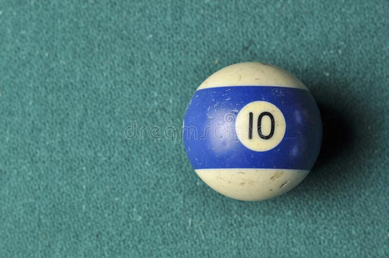 Den gamla billiardbollen nummer 10 gjorde randig vitt och bl?tt p? den gr?na billiardtabellen, kopieringsutrymme royaltyfria foton