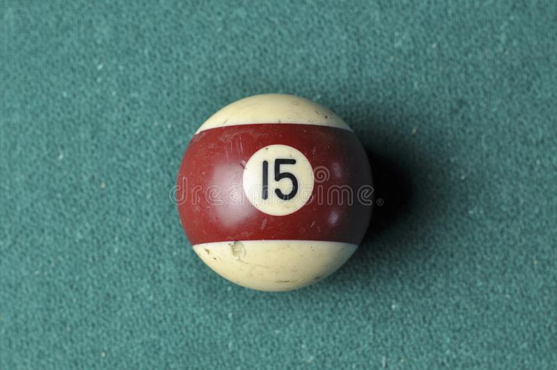 Den gamla billiardbollen nummer 12 gjorde randig vitt och brunt på den gröna billiardtabellen, kopieringsutrymme arkivbild