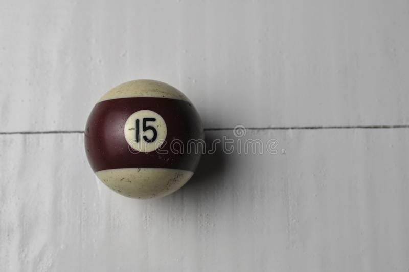 Den gamla billiardbollen nummer 15 gjorde randig vitt och brunt på vit trätabellbakgrund, kopieringsutrymme royaltyfri fotografi