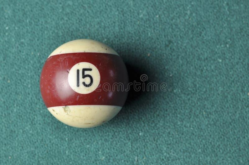Den gamla billiardbollen nummer 12 gjorde randig vitt och brunt p? den gr?na billiardtabellen, kopieringsutrymme royaltyfri fotografi