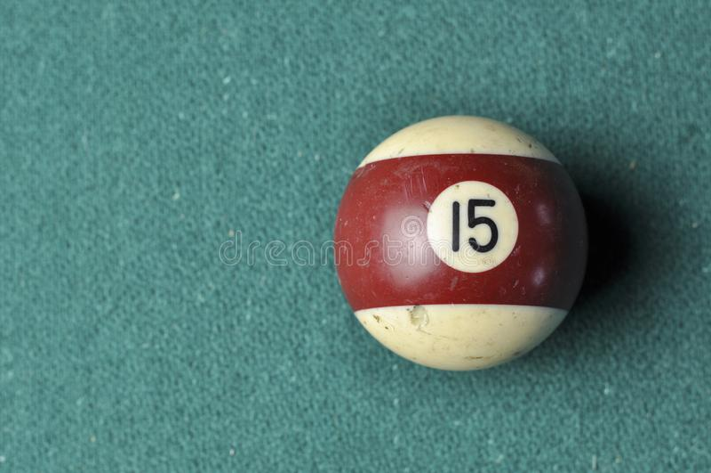 Den gamla billiardbollen nummer 12 gjorde randig vitt och brunt p? den gr?na billiardtabellen, kopieringsutrymme arkivbilder