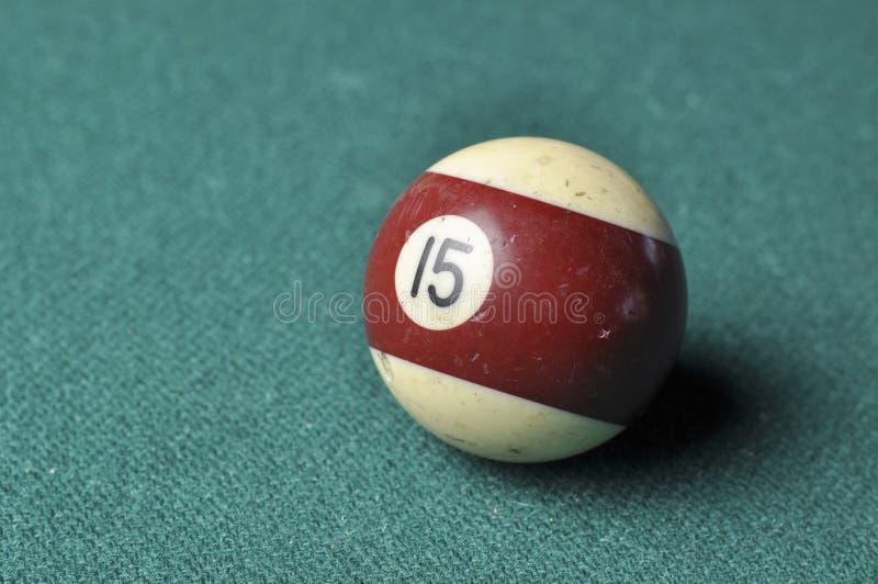 Den gamla billiardbollen nummer 12 gjorde randig vitt och brunt p? den gr?na billiardtabellen, kopieringsutrymme arkivbild
