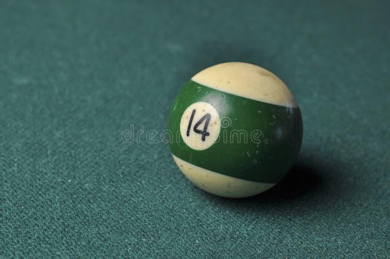 Den gamla billiardbollen nummer 14 gjorde randig vitt och grönt på den gröna billiardtabellen, kopieringsutrymme arkivbilder
