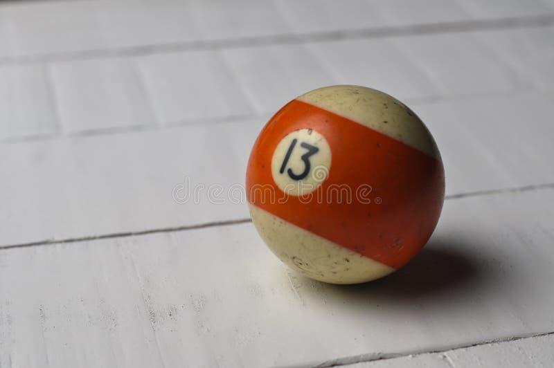 Den gamla billiardbollen nummer 13 gjorde randig vitt och orange på vit trätabellbakgrund, kopieringsutrymme arkivfoto