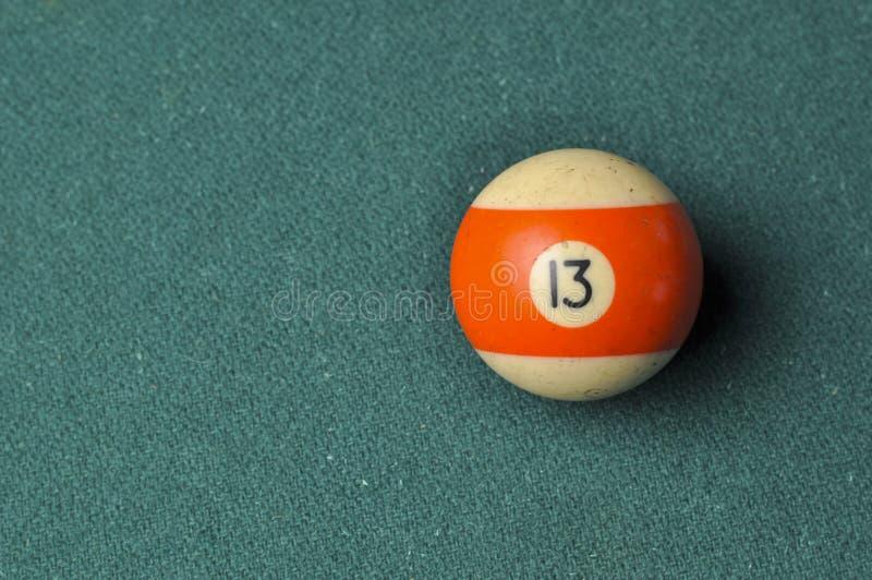 Den gamla billiardbollen nummer 13 gjorde randig vitt och orange p? den gr?na billiardtabellen, kopieringsutrymme royaltyfria bilder