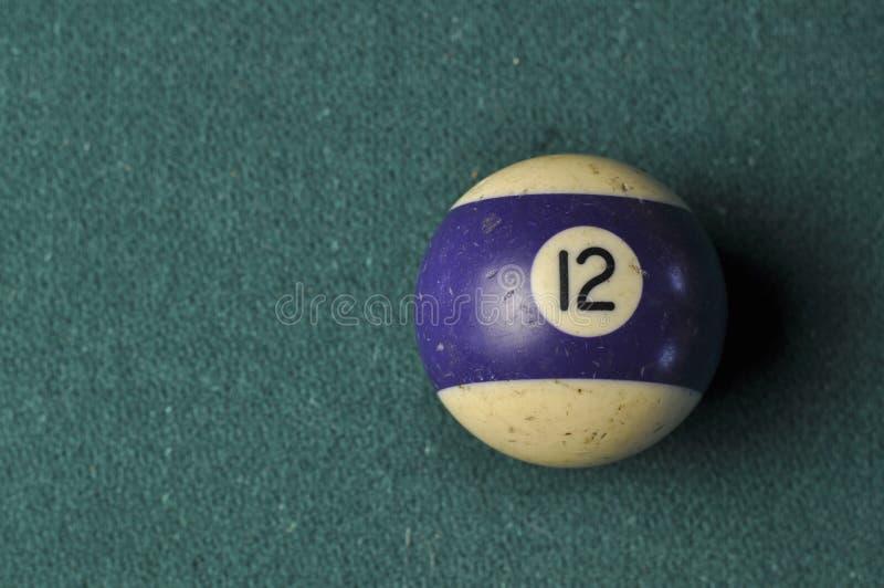 Den gamla billiardbollen nummer 12 gjorde randig vitt och purpurfärgat på den gröna billiardtabellen, kopieringsutrymme arkivfoton