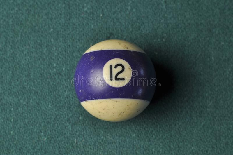 Den gamla billiardbollen nummer 12 gjorde randig vitt och purpurf?rgat p? den gr?na billiardtabellen, kopieringsutrymme royaltyfri foto