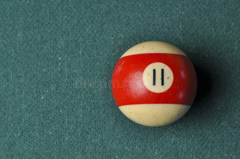 Den gamla billiardbollen nummer 11 gjorde randig vitt och rött på den gröna billiardtabellen, kopieringsutrymme royaltyfria foton