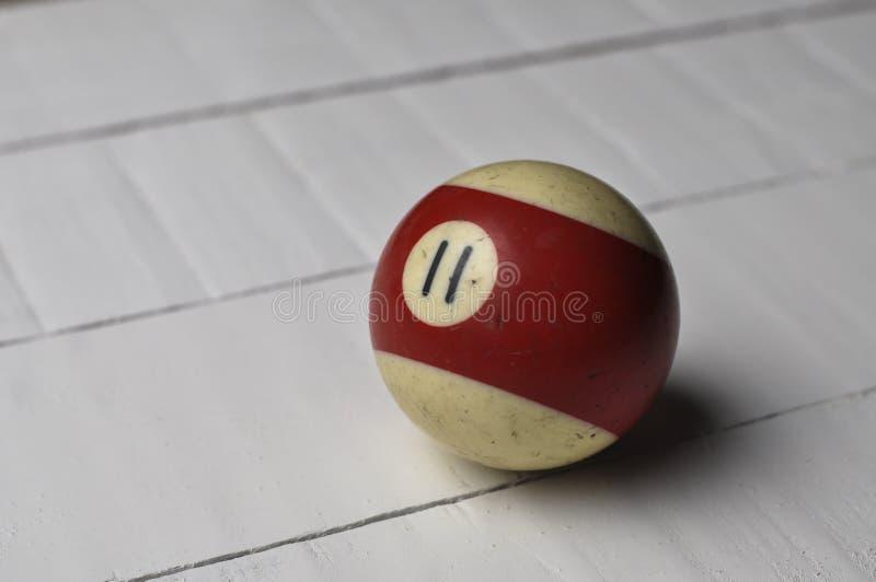 Den gamla billiardbollen nummer 11 gjorde randig vitt och rött på vit trätabellbakgrund, kopieringsutrymme royaltyfria bilder