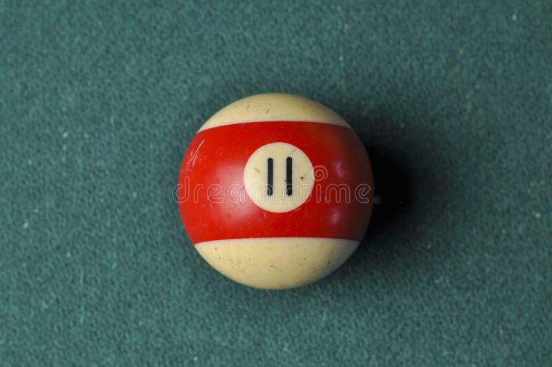Den gamla billiardbollen nummer 11 gjorde randig vitt och r?tt p? den gr?na billiardtabellen, kopieringsutrymme fotografering för bildbyråer