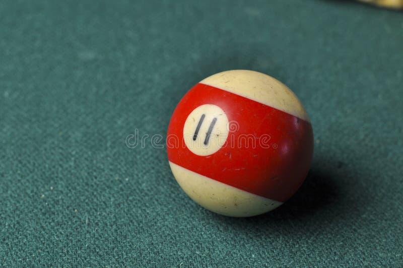 Den gamla billiardbollen nummer 11 gjorde randig vitt och r?tt p? den gr?na billiardtabellen, kopieringsutrymme royaltyfri bild