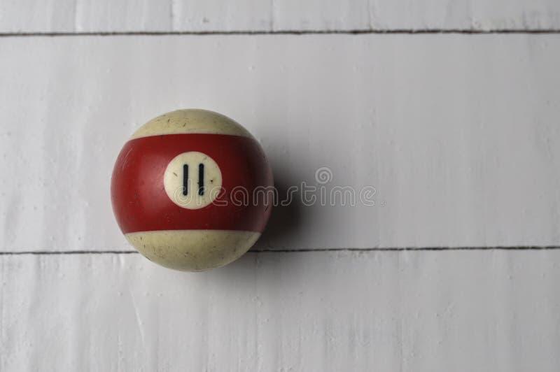 Den gamla billiardbollen nummer 11 gjorde randig vitt och r?tt p? vit tr?tabellbakgrund, kopieringsutrymme royaltyfria foton
