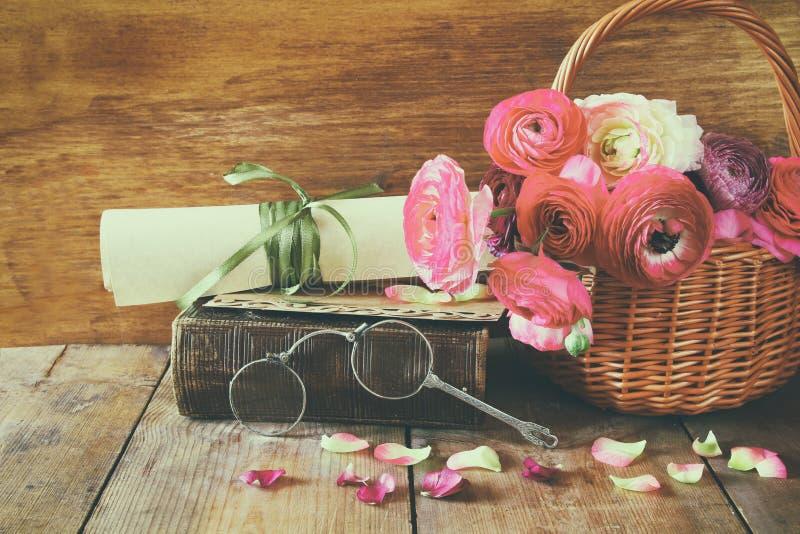 Den gamla boken och exponeringsglas bredvid härligt fält blommar arkivfoto