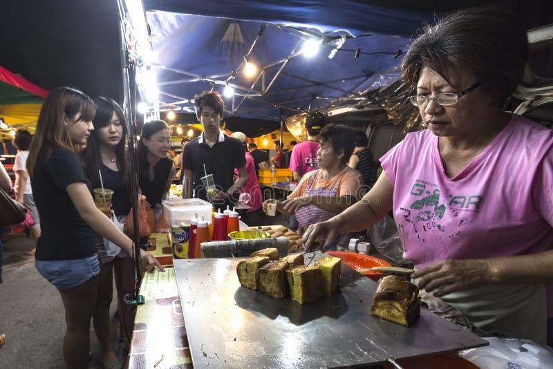 Den gamla damen förse med rutor-stekte mjukt bröd på PJ Pasar Malam fotografering för bildbyråer
