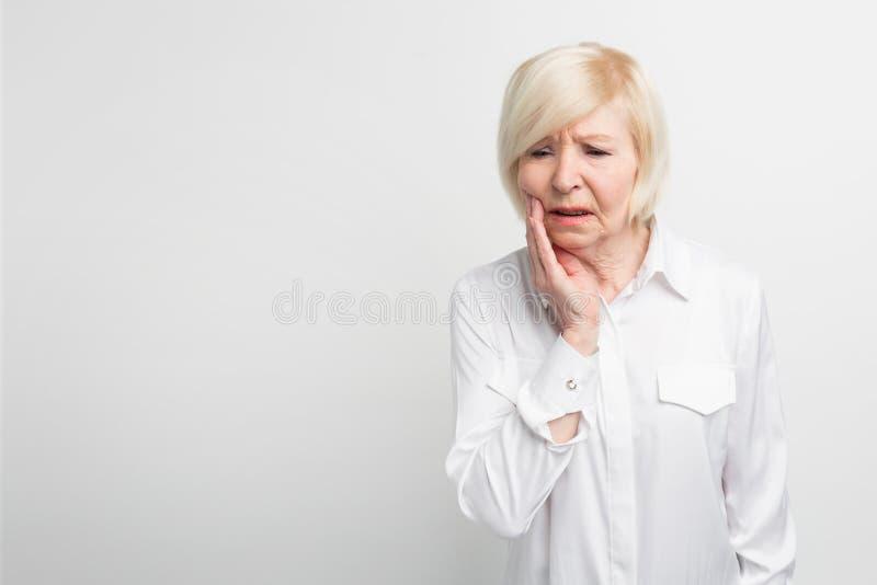 Den gamla damen lider från en tandvärk Det startade att göra ont plötsligt Hon behöver gå till tandläkaren på vit royaltyfri bild