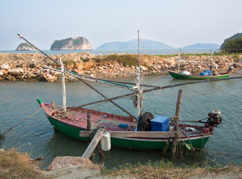 Den gamla fiskebåten anslutas på bakgrunden av kusten vaggar arkivbild