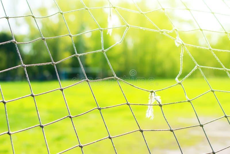 Den gamla fotbollporten med hålet, på bakgrund av gröna fält arkivbild
