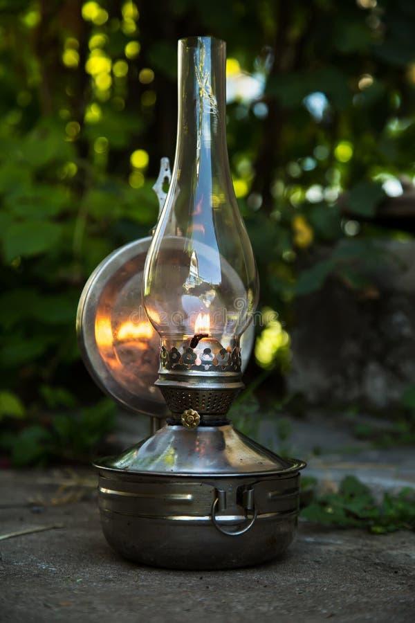 Den gamla fotogenlampan står på jordningen, utomhus royaltyfria foton