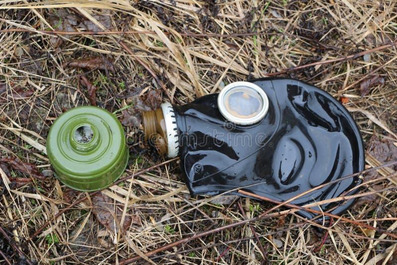 Den gamla gasmasken ligger på det vissnade gräset efter regnet begrepp: biologiskt och gasa fara, slutet av världen, apokalypens, royaltyfri fotografi