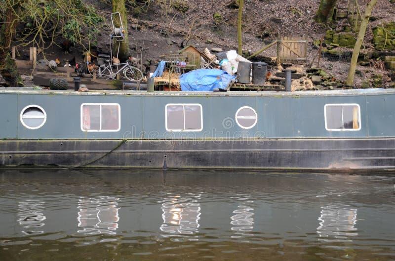 Den gamla gröna husbåten förtöjde på en kanal som reflekterar i vattnet arkivbilder