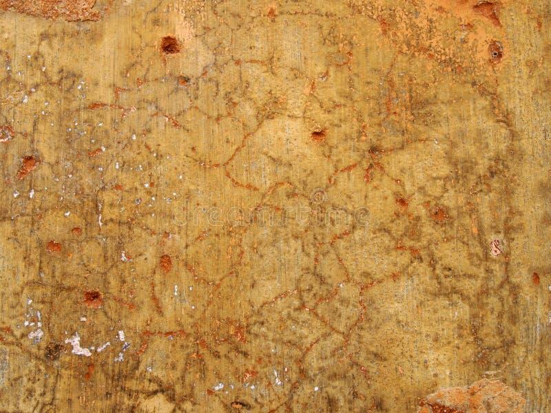 Den gamla grova gula ockran färgade sprucken urblekt nedfläckad målad murbrukväggtextur med röda och orange detaljer arkivbild