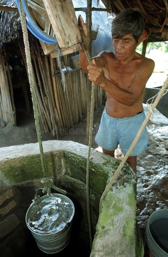 Den gamla guatemalanska indiska mannen får vatten från brunnen royaltyfri bild