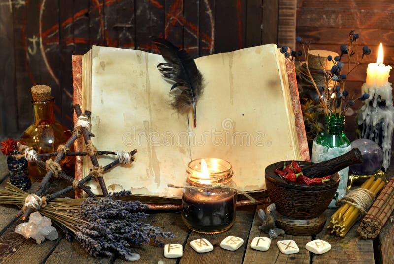 Den gamla häxaboken med tomma sidor, lavendel blommar, pentagramen, och häxeri anmärker arkivfoton