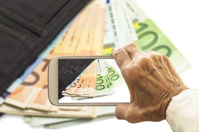 Den gamla handen tar en bild av plånboken med eurosedlar på smart arkivfoton