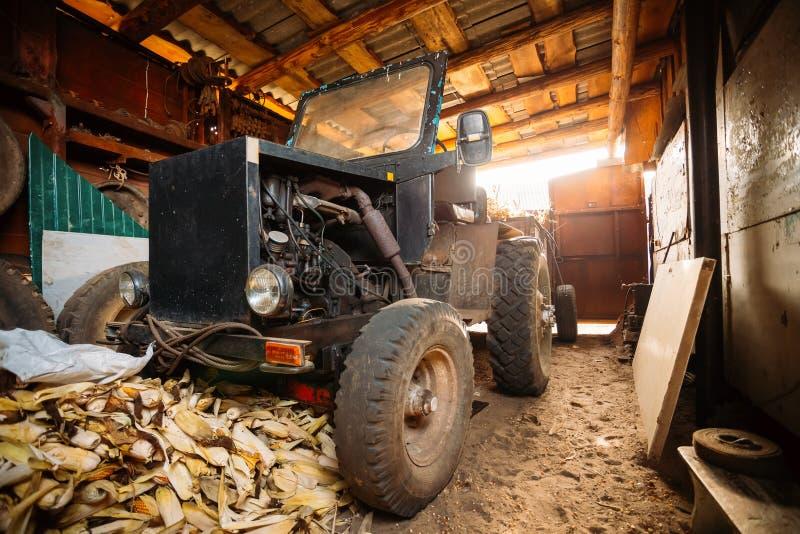 Den gamla hemlagade traktoren står i ladugård fotografering för bildbyråer