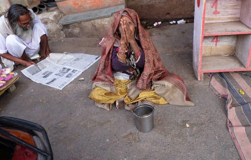 Den gamla indiska tiggaren väntar på allmosa på en gata i Pushkar, Indien royaltyfri bild