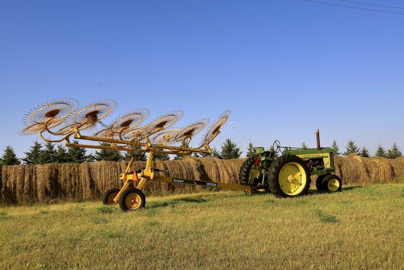 Den gamla John Deer 620 traktoren och hjulet krattar fotografering för bildbyråer
