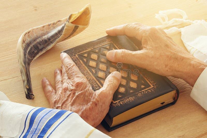 Den gamla judiska mannen räcker att rymma en bönbok som ber, bredvid tallit- och shofarhornet Judiska traditionella symboler slåe arkivbild