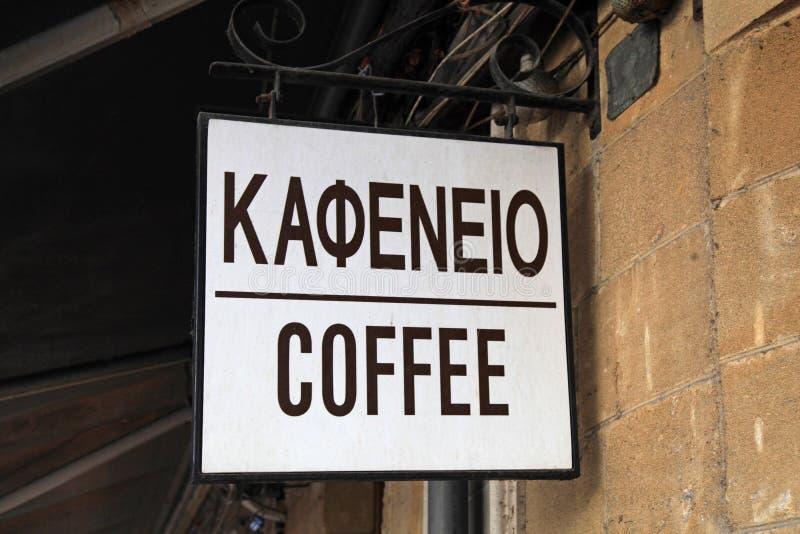 Den gamla kaffeskylten med grek och engelska smsar royaltyfri foto