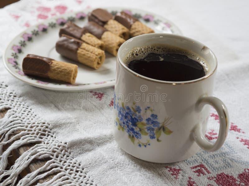 Den gamla kanstödda koppen med svart kaffe på lantlig bordduk med plat royaltyfri bild