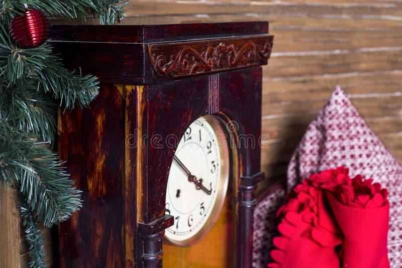 Den gamla klockan i en träask mot bakgrunden av en röd pläd och enfärgad kudde, står nära ett träd för nytt år arkivbild